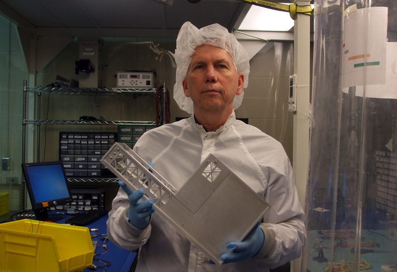 NSS Director and Team Member Dean Larson holds the Cislunar Explorers Spacecraft in the Cornell University Clean Room