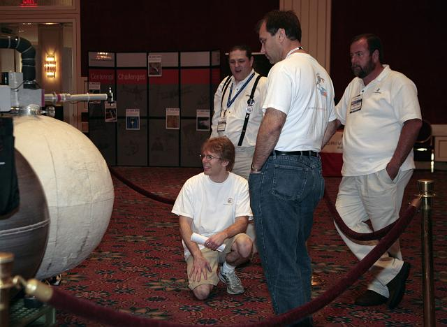 Armadillo Aerospace CEO John Carmack (kneeling) confers with Armadillo Aersopace team members Phil Eaton (center) and Tommy Bishop (R) at the International Space Development Conference