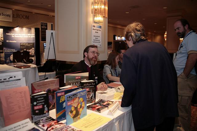 Author Father James Heiser signs books at the Authors Table at the International Space Development Conference