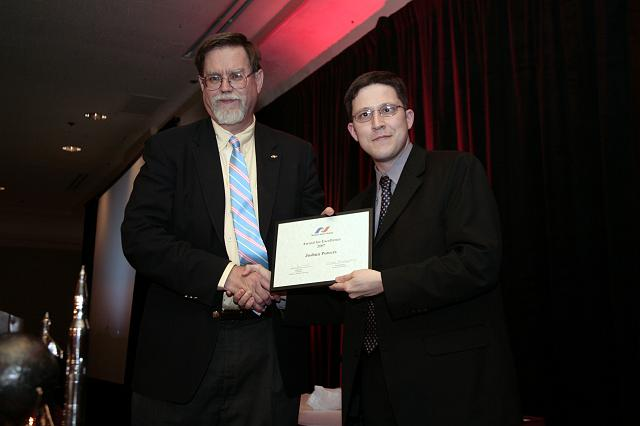 Josh Powers accepts an NSS Award for Excellence from NSS Senior Vice President Mark Hopkins at the International Space Development Conference