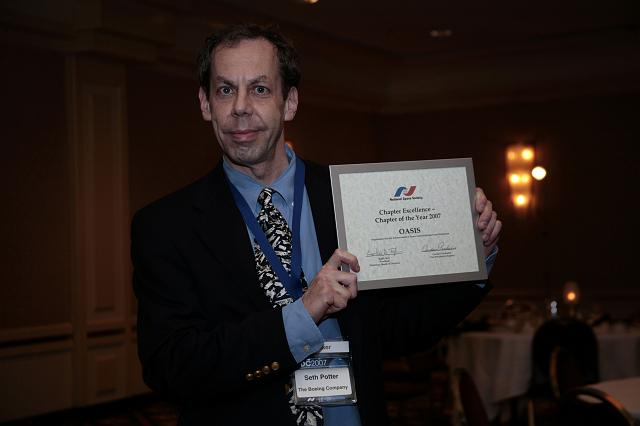 Seth Potter of the NSS OASIS chapter holds the NSS Chapter Excellence: Chapter of the Year 2007 Award presented to the OASIS chapter at the International Space Development Conference