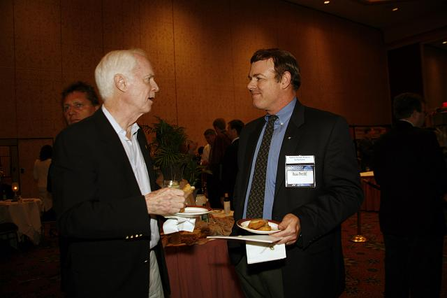 Apollo Astronaut and B612 Foundation founder Rusty Schweickart talks with Russ Prechtl at the Space Venture Finance Symposium reception, a part of the International Space Development Conference