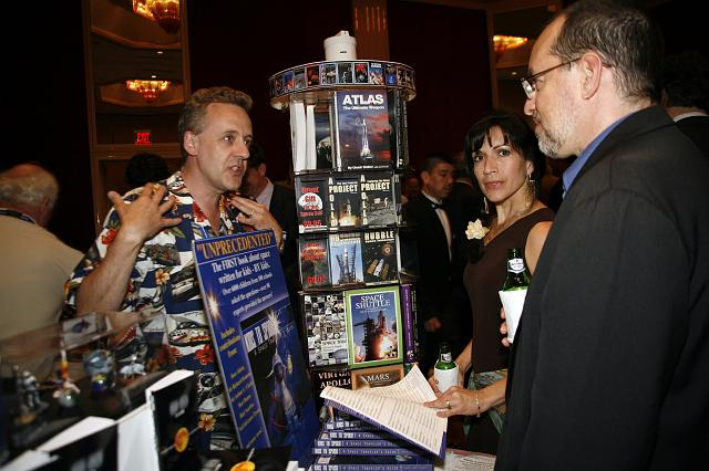 Richard Godwin (L), founder and co owner of CG Publishing and NSS Director, talks with visitors at the Red Planet Adventures exhibit at the Space Venture Finance Symposium reception, a part of the International Space Development Conference